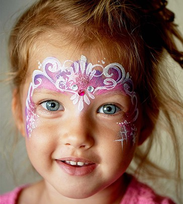 6 years old boy with blue eyes face painting of a cat or tiger.Pretty exciting blue-eyed girl of 2 years with a face painting